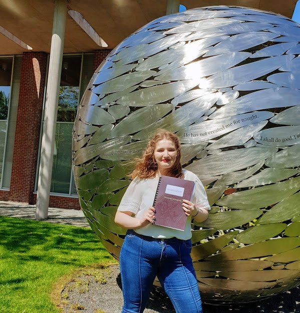 Graduate Elizabeth Dissertation Hand in day standing outside the Globe
