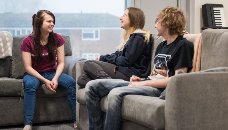 2-female-students-and-1-male-student-sitting-on-sofas-at-newman-university-halls