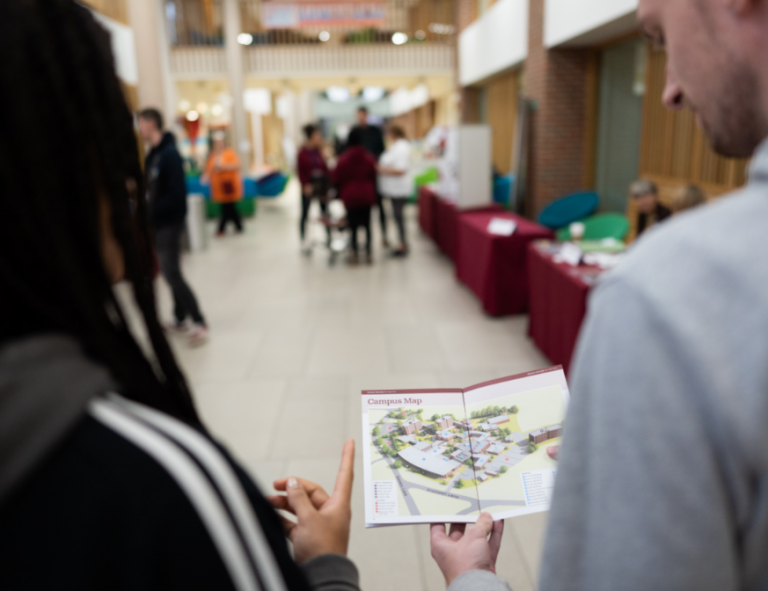 People at an Open Day holding a map