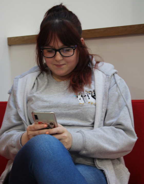 Female student looking at phone and sitting down