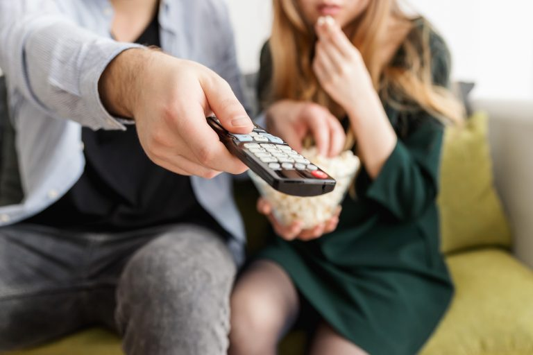 man holding remote control and woman eating popcorn