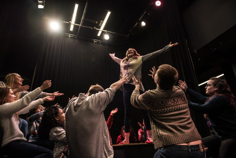 Students in drama studio, one student with hands in the air