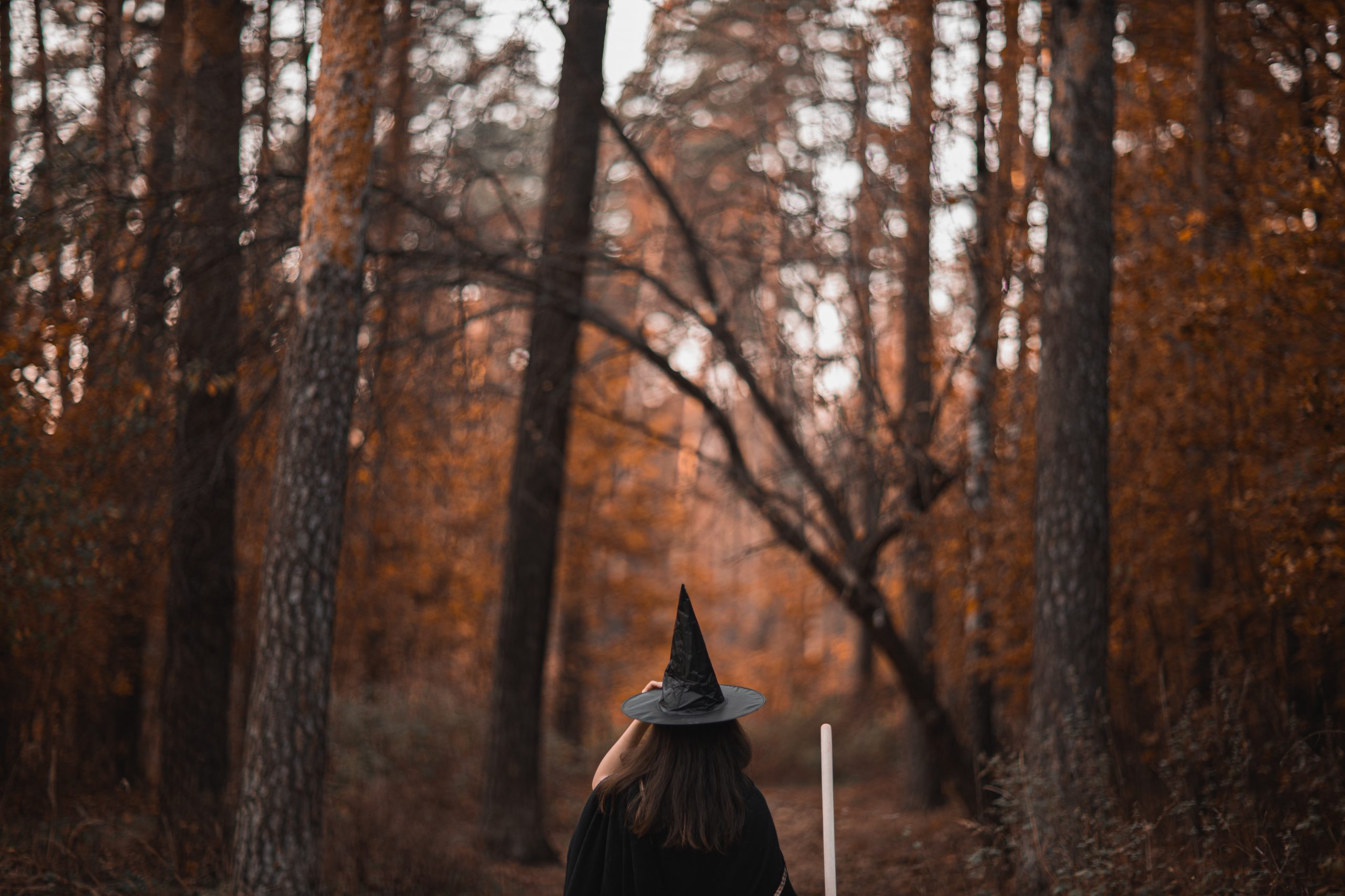 girl dressed as witch in forest
