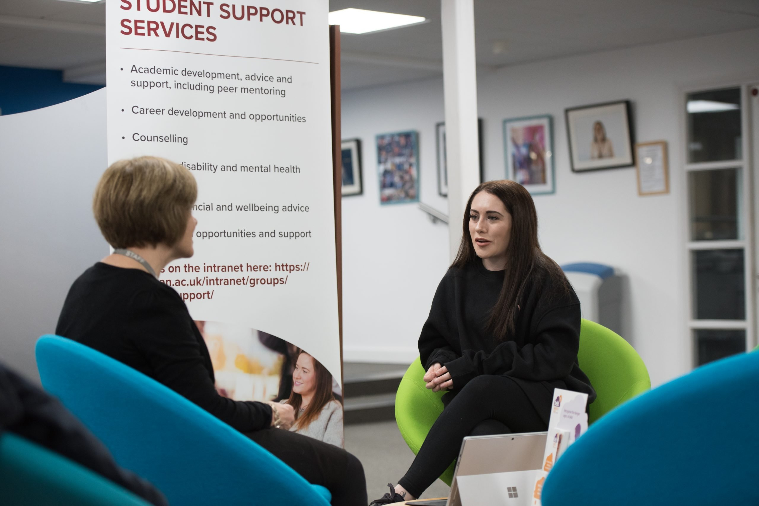 Staff and student sitting and talking by Student Support Services banner