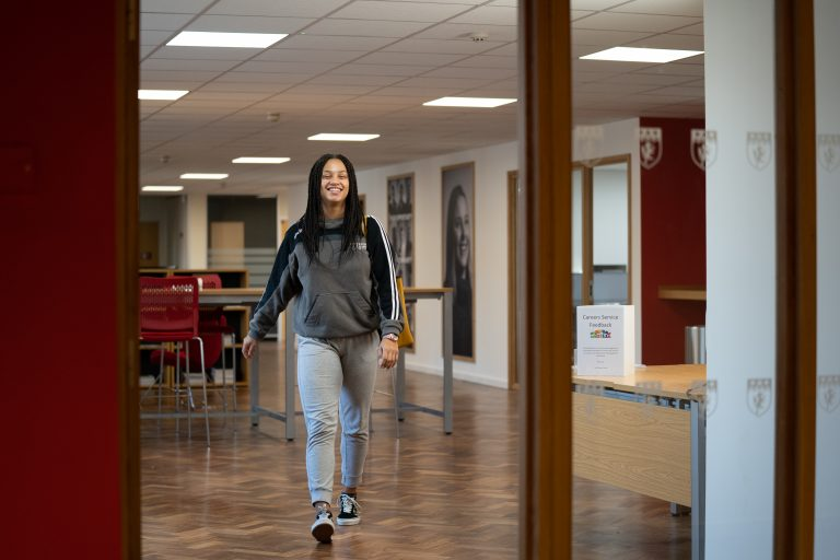 Female student smiling and walking out of careers hub