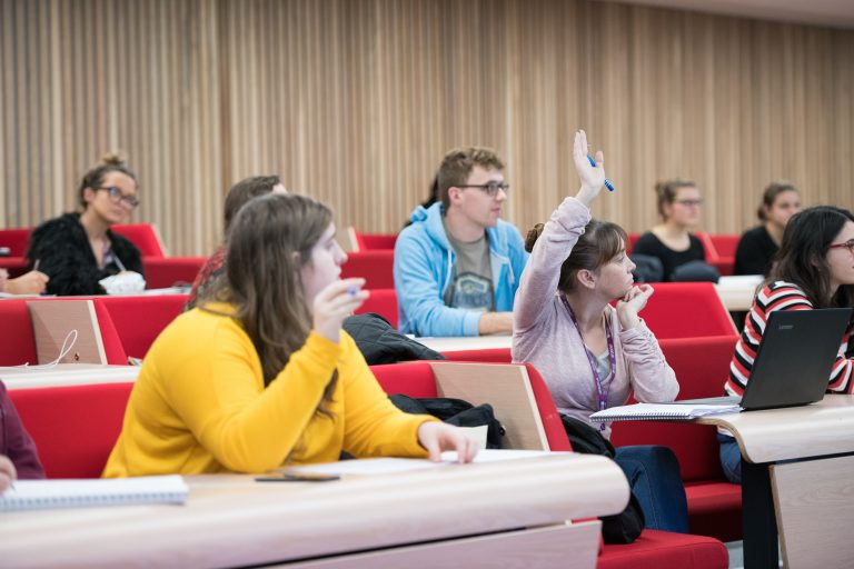 Students in lecture theatre, one student with hand up