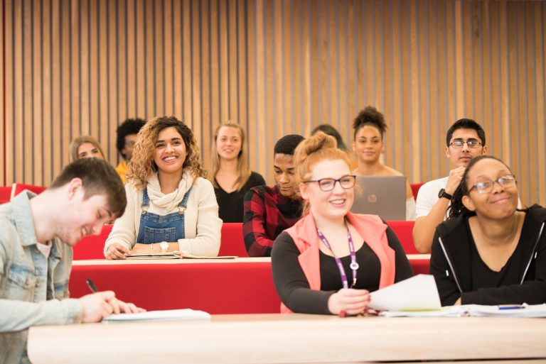 students in lecture theatre working and smiling