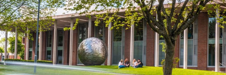 Front of Newman University campus on a spring day as students sit on the grass