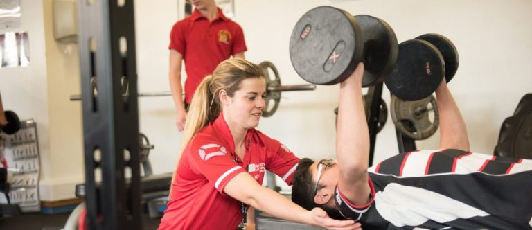 sport trainee teacher supporting student with free weights