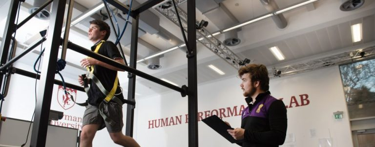 sport student on treadmill as another student analyses performance