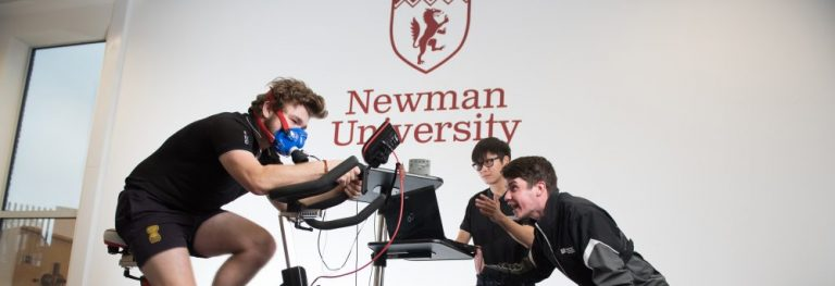sports student on a static bike with other students encouraging him and analysing performance