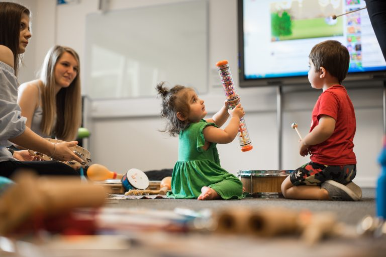 early childhood education and care students with young children in music lesson