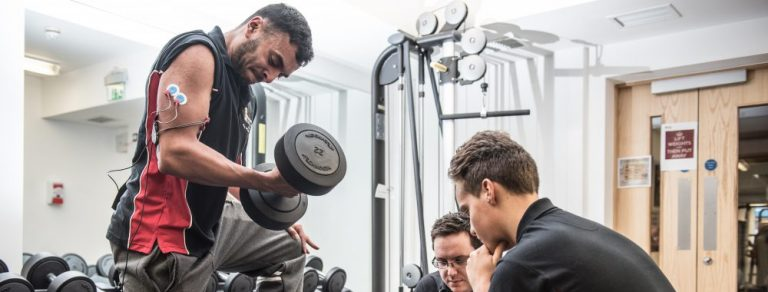students and lecturer performing sports analysis on student lifting weights