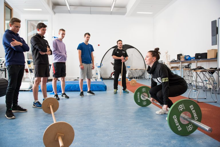 sport student lifting barbell as other students watch