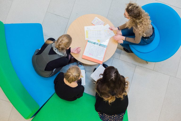 students studying in the atrium with books on the table