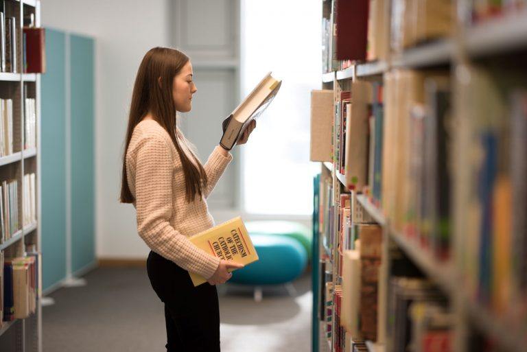 student in the library choosing books